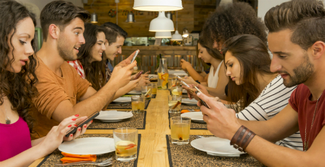 group-at-restaurant-on-phones.jpg
