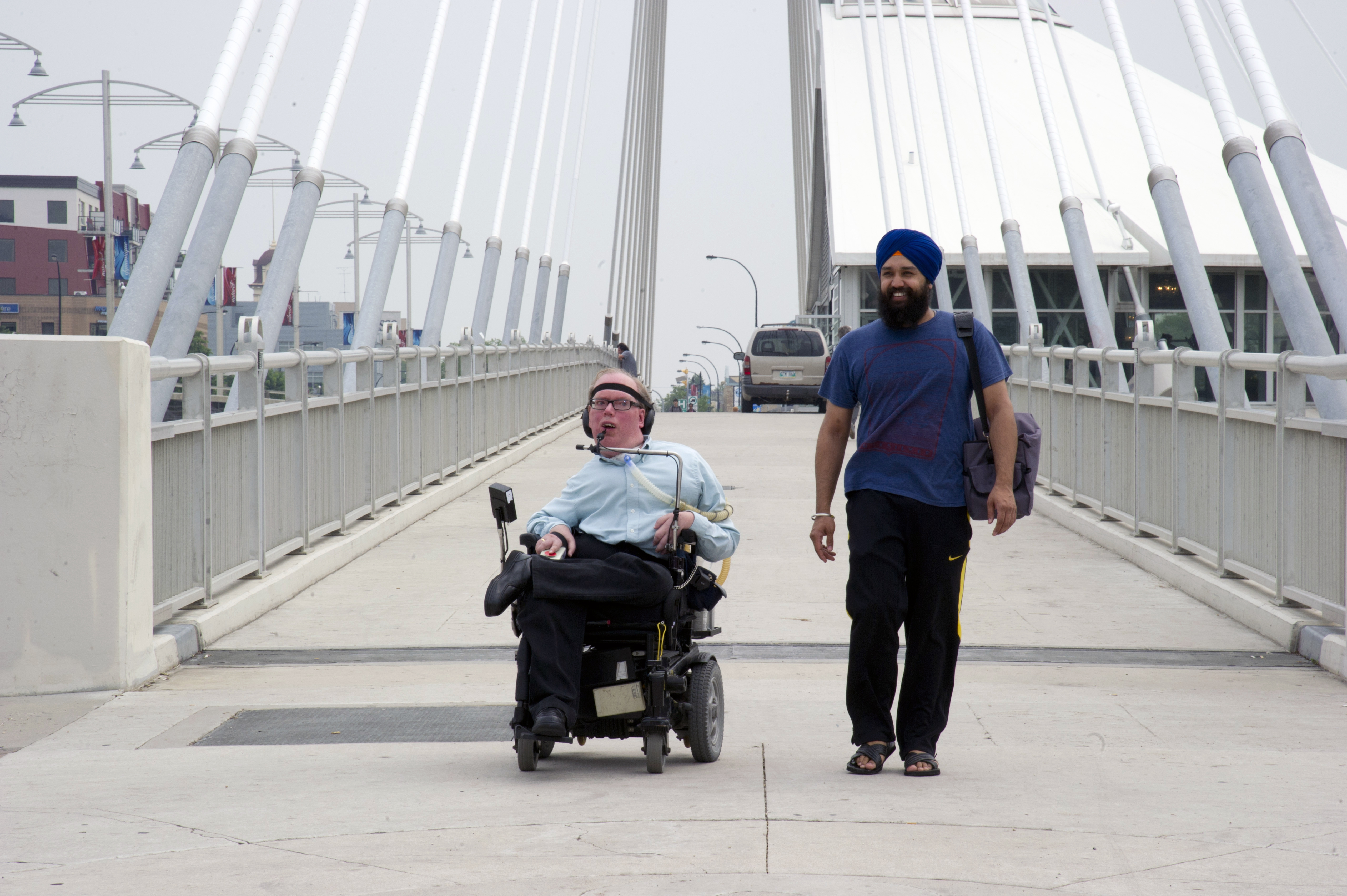 A man sits in a wheelchair and another man stands to his left on a bridge.JPG
