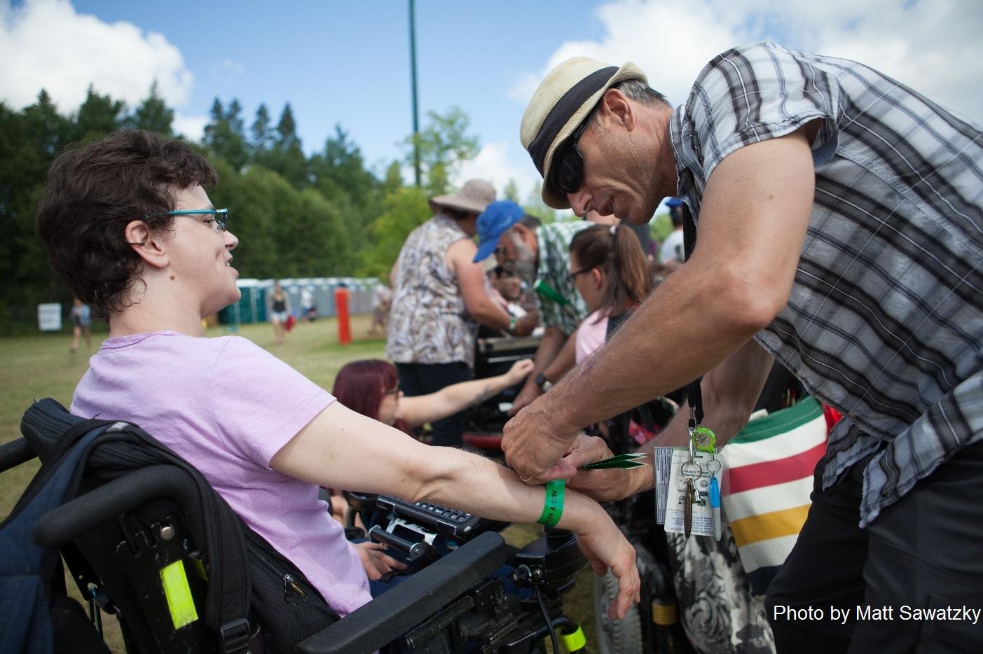 Woman in a wheelchair being assisted with her wristband by a Winnipeg Folk Festival volunteer. Photo by Matt Sawatzky.